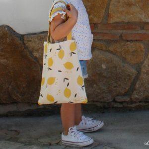 Niña con bolsa de la compra infantil de algodón orgánico y estampado de limones - Limón & me