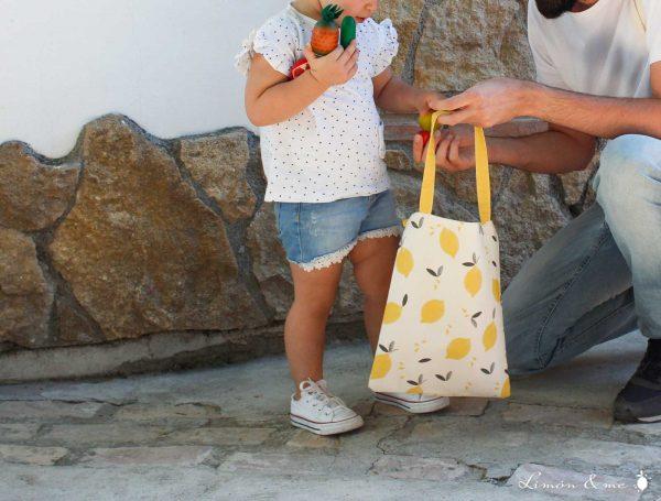 Niña llenando bolsa de la compra de algodón orgánico - Limón & me