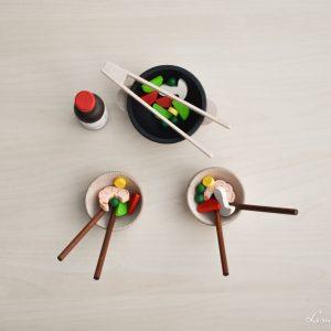 Comida asiática con wok, cuencos, palillos y pinzas de madera - Erzi